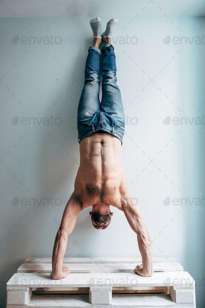 Man posing on camera, standing upside down