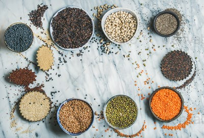 Various raw uncooked grains, beans, cereals in bowls, copy space