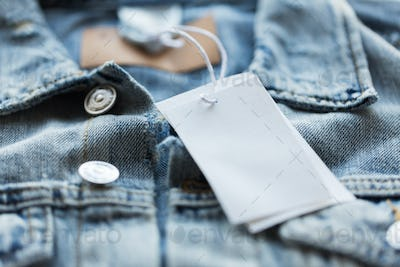 close up of denim jacket with white price tag