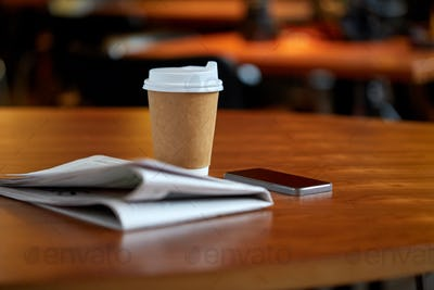 coffee cup, smartphone and newspaper on cafe table