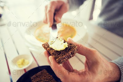 close up of hands applying butter to bread