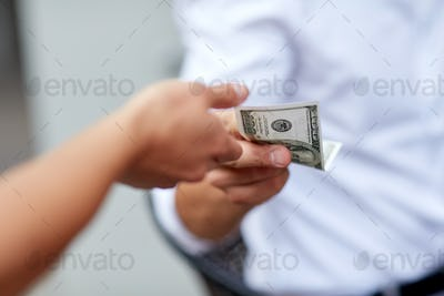 close up of hands giving and receiving dollar money