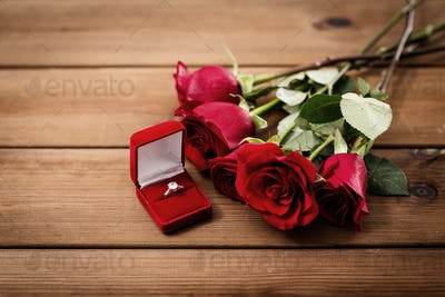 close up of diamond engagement ring and red roses