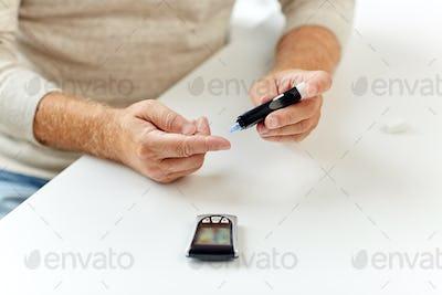 senior man with glucometer checking blood sugar