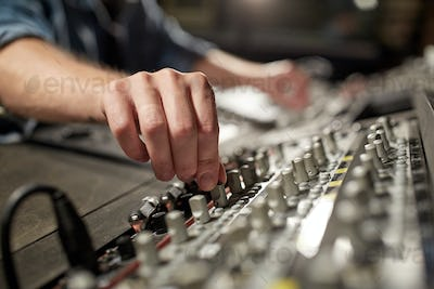 man using mixing console in music recording studio
