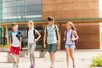 group of happy elementary school students walking