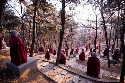 Stone Monk Statues wearing mantles at chinese forest