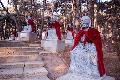 Forest with stone statues of monks wearing red mantles