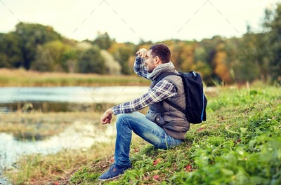 smiling man with backpack resting on river bank