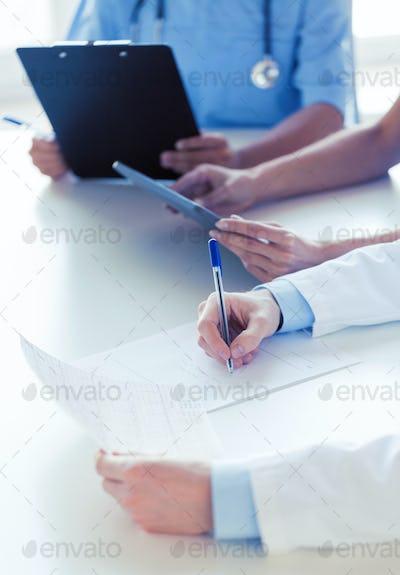 close up of happy doctors at seminar or hospital