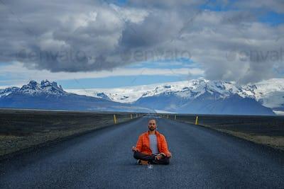 Travel hitchhiker man meditating on a road