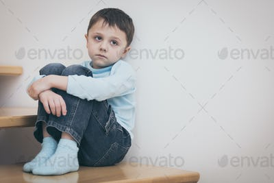 one sad little boy sitting on the stairs in house at the day tim