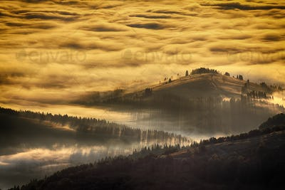Sunrise landscape of foggy and cloudy mountain valley