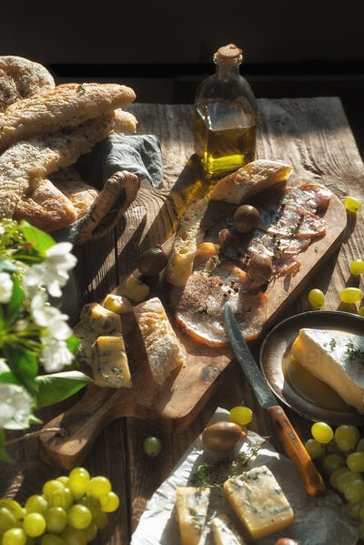 Homemade bread, cheese, olives, jamon, flowers on old boards