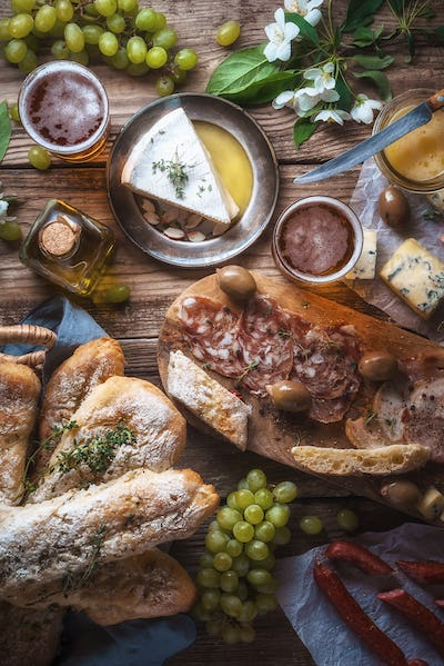 Homemade baguette, cheese, olives, grapes, flowers on old boards