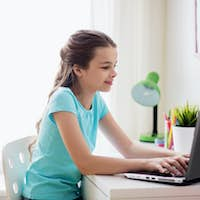 girl typing on laptop at home
