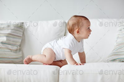 little baby in diaper crawling along sofa at home