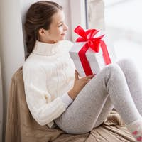 girl with gift sitting on sill at home window