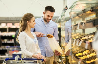 happy couple with shopping cart at grocery store