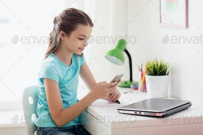 girl with laptop and smartphone texting at home