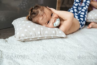 Cute little girl child indoors with nipple lies on bed
