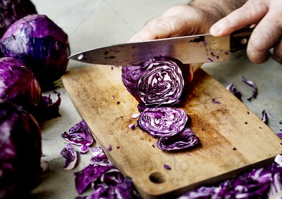 Closeup of hand with knife cutting red cabbage