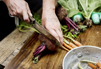 Closeup of hand with knife cutting fresh vegetable