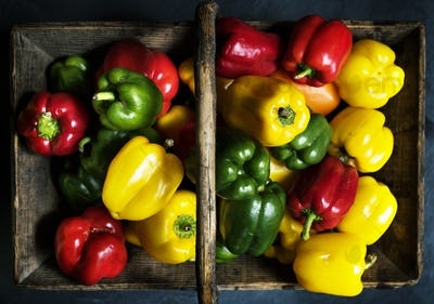 Aerial view of fresh sweet peppers in wooden basket