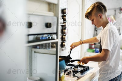 Young caucasian man cooking in the kitchen