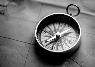Closeup of metallic compass on the map journey planning grayscal