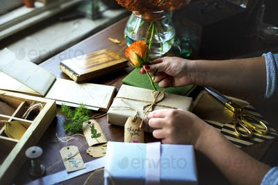 Hands diy wrapping gift box on wooden table