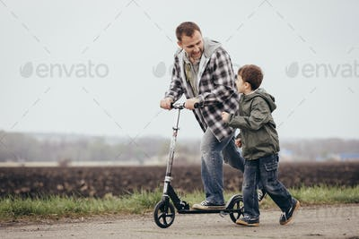 Father and son walking on the road at the day time.