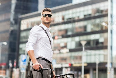 young man with bicycle on city street