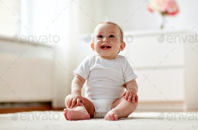 happy baby boy or girl sitting on floor at home