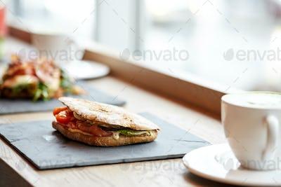 salmon panini sandwich on stone plate at cafe
