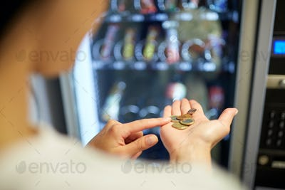 woman counting euro coins at vending machine