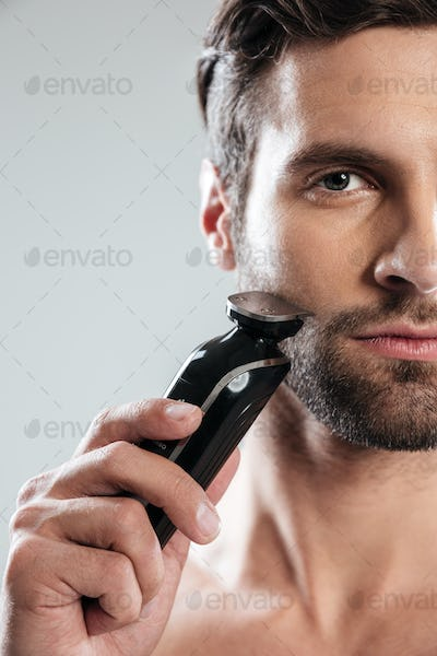 Handsome young man holding electric razor