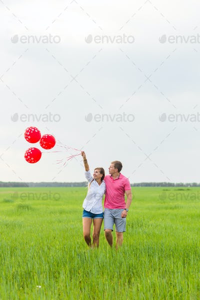 beautiful young couple hugging and kissing in a field with colored balloons
