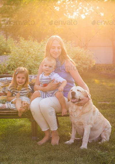 Mother and her daughter and son in the garden with a golden retriever dog