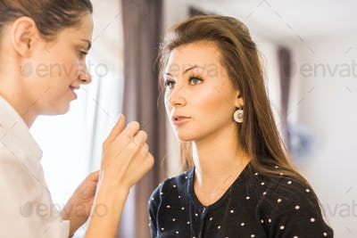 woman getting professional make-up with brush