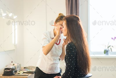 Woman making beauty and make up treatment in a saloon. Concept about beauty and people