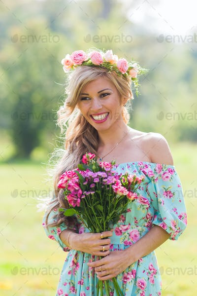 Close-up portrait of beautiful blonde girl holding bouquet of flowers at the countryside