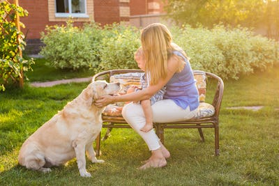 Mother and son together having fun in the summer park playing with a golden retriever.