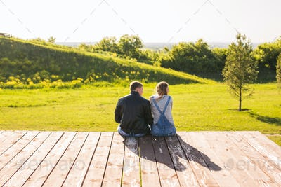 Love couple hugging on a pier in nature back view