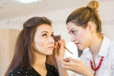 portrait of beautiful woman getting professional make-up with brush