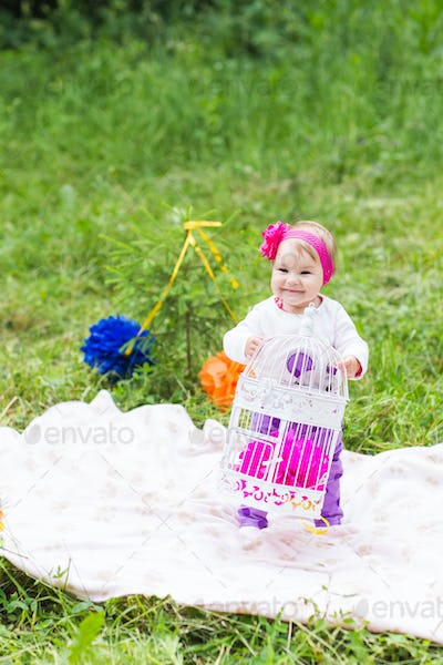 baby girl playing on the green grass, family picnic close-up