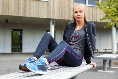 Confident Woman In Sportswear Listening Music On Bench