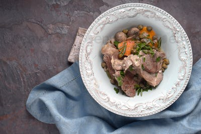 Meat blanquette in the ceramic plate on the stone background
