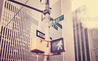 Retro stylized crosswalk signal and traffic sign post in NYC.
