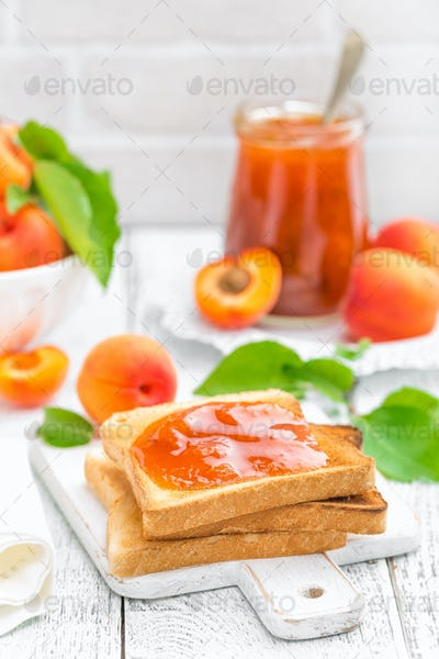 Toasts of bread with apricot jam and fresh fruit with leaves on white wooden table. Tasty breakfast.